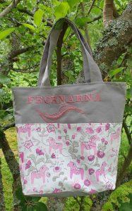Rosa väska med dalahästar som motiv